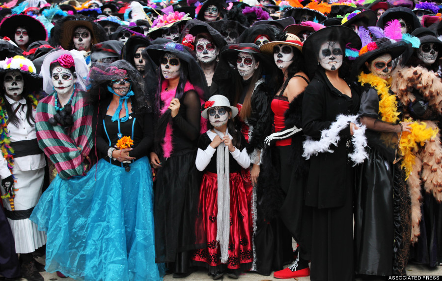 "Women dressed as iconic Mexican ""Catrinas"" gather in an attempt to set a record for the most Catrinas in one place during Day of the Dead celebrations in Mexico City, Saturday, Nov. 1, 2014. The figure of a skeleton wearing an elegant broad-brimmed hat was first done as a satirical engraving by artist Jose Guadalupe Posada sometime between 1910 and his death in 1913. (AP Photo/Marco Ugarte)"